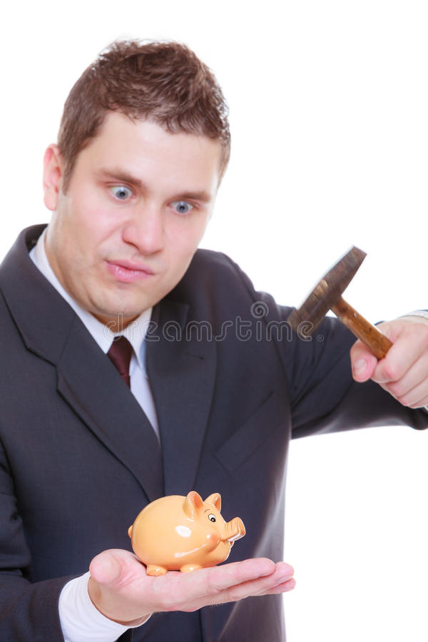 Man trying to break piggy bank with hammer royalty free stock images