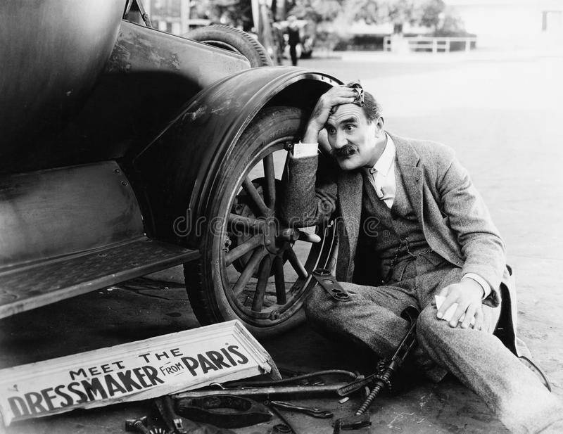 Man trying to fix broken car. (All persons depicted are no longer living and no estate exists. Supplier grants that there will be no model release issues royalty free stock photography