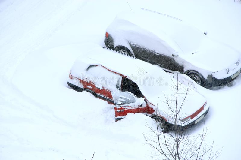 Man trying to free his car from snowy captivity. Parked cars covered with snow. Bad weather in town. Snowy day. Urban scene. Weather concept. Automobiles royalty free stock images