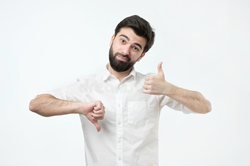 Man trying to make a desicion making good or bad sign. Undecided between yes or not stock photo