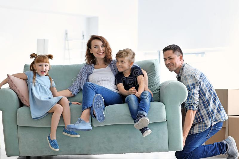 Man trying to move sofa with his family at new home stock images