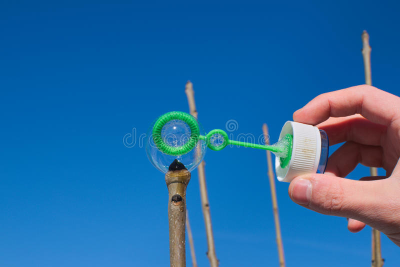 Man trying to put a single soap bubble on top of a plant stem stock photography