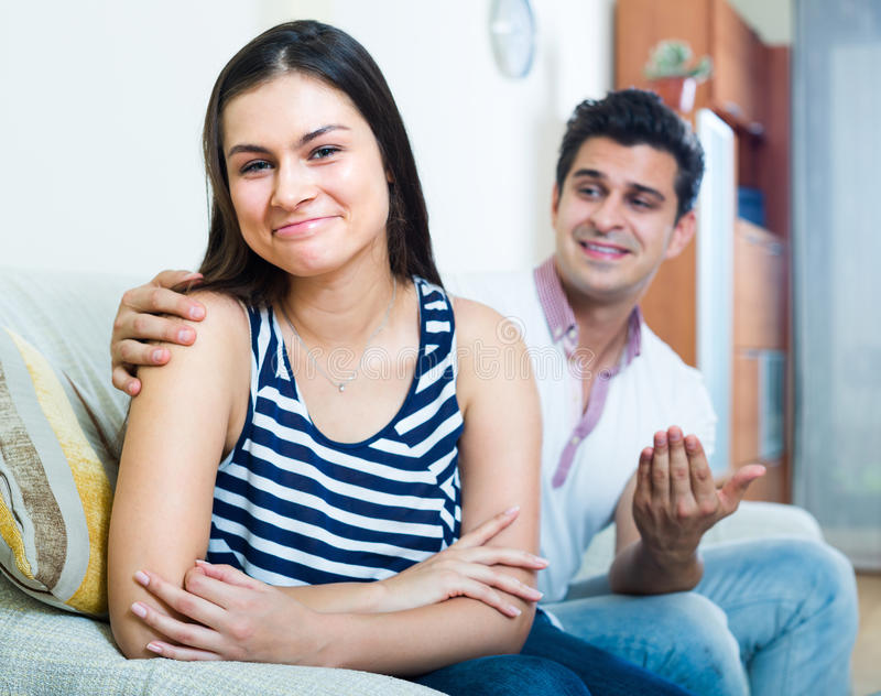 Man trying to reconcile with woman. Portrait of young women and men making efforts to reconcile with her at home royalty free stock photo