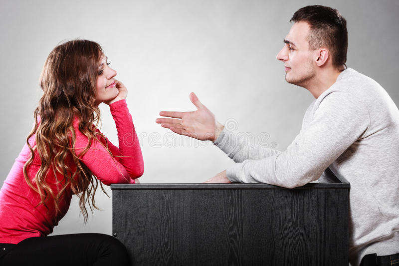 Man trying to reconcile with woman after quarrel. Man trying to reconcile with woman. Couple making up after quarrel. Husband reaching out to wife stock image