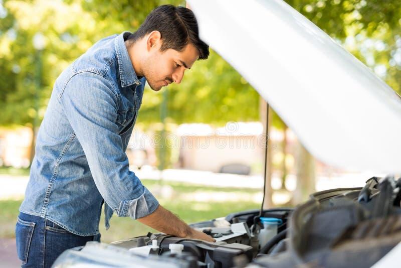 Man trying to repair his car stock photo