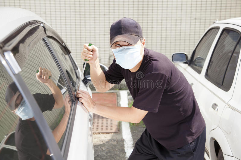 Man trying to steal a car. Man in mask trying to steal a car royalty free stock images