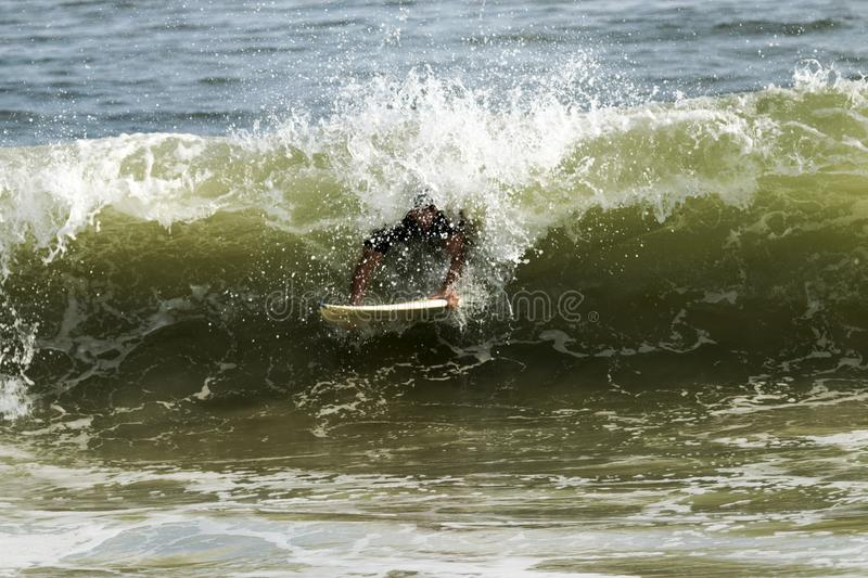 Surfer blurred by the water of the wave all around him. A man trying to surf off of Fire Island National Seashore is covered by the wave he is trying to ride stock images