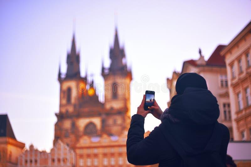 Man/turist som tar foto av en monument med mobiltelefonen Prague Ung man med ryggsäcken som tar bilder av gatan på smart p arkivfoton