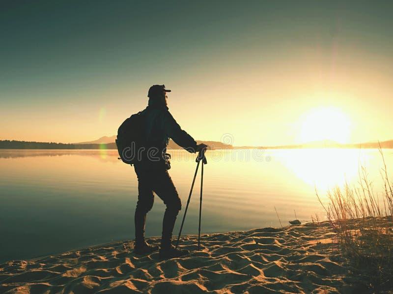 Man turisten med en ryggsäck och trekking poler som står på den sandiga stranden Fotvandraren tycker om royaltyfria bilder