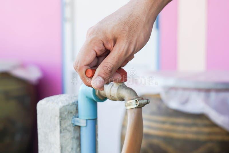 Man turn water tap off for saving environment royalty free stock image