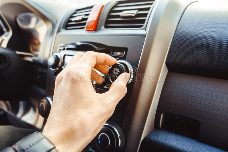 Car radio in the car. Man turning button of radio in car royalty free stock photos