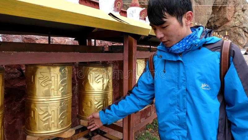 Man turning golden prayer wheel stock image