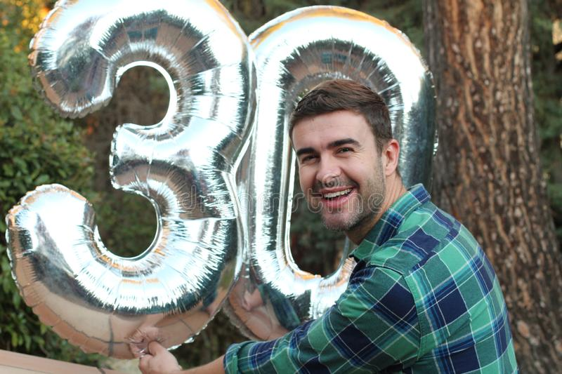 Man turning 30 holding inflatable balloons stock photos