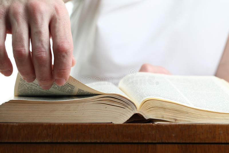 Man turning the page of the Bible. Shallow dof royalty free stock photography