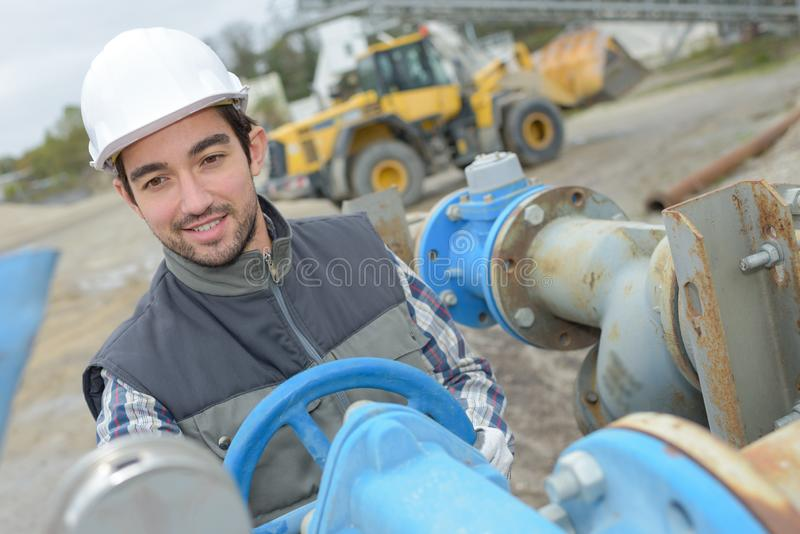 Man turning wheel on industrial pipework stock images