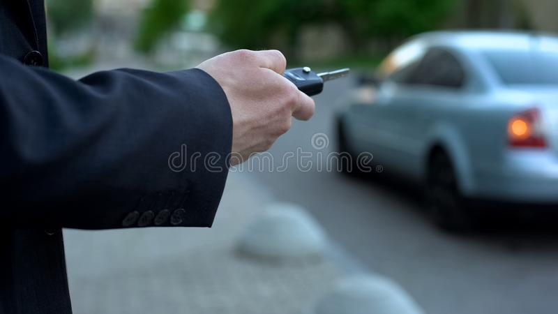 Man turns on car alarm, security concept, risk of hijacking car parked on street royalty free stock photo