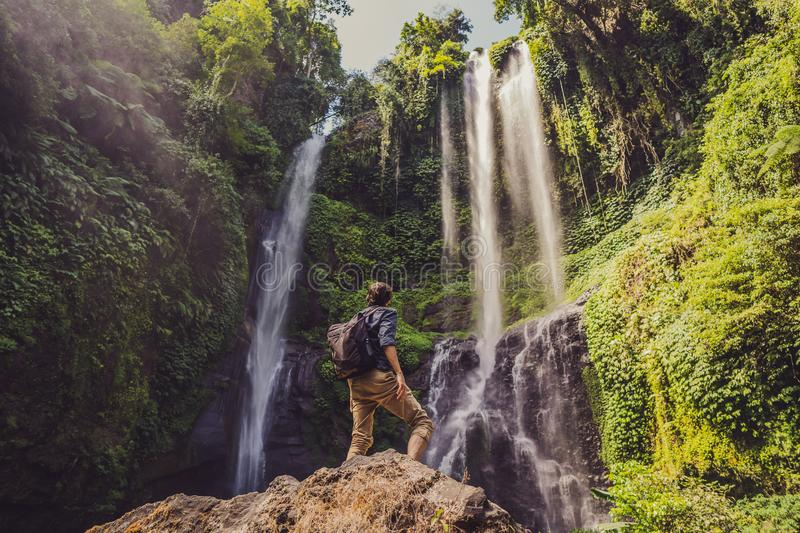Man in turquoise dress at the Sekumpul waterfalls in jungles on Bali island, Indonesia. Bali Travel Concept stock photography