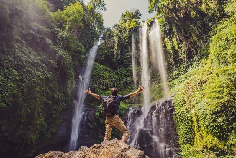 Man in turquoise dress at the Sekumpul waterfalls in jungles on Bali island, Indonesia. Bali Travel Concept stock photo