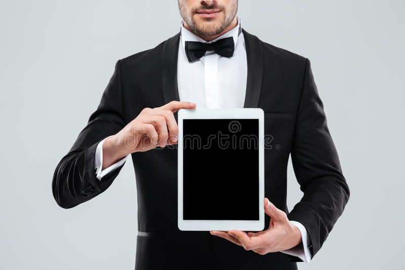 Man in tuxedo with bowtie holding blank screen tablet. Closeup of handsome young man in tuxedo with bowtie holding blank screen tablet stock photos
