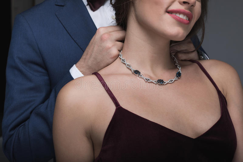 Man in tuxedo putting necklace on his girlfriend stock photography
