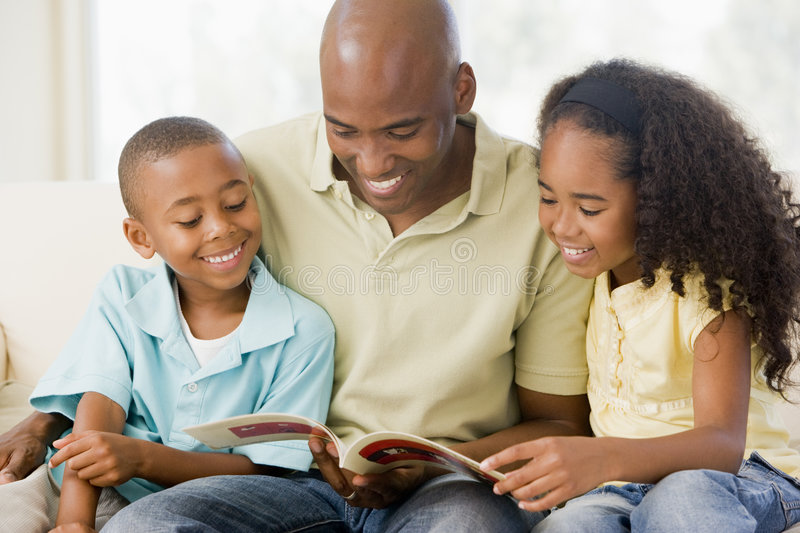 Man and two children sitting in living room stock photo
