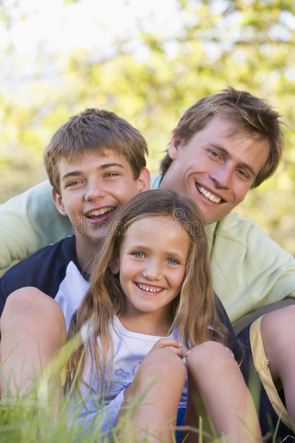 Man with two children sitting outdoors smiling royalty free stock images