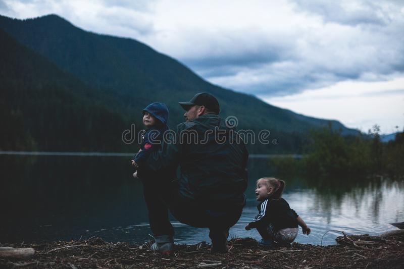 Man With Two Kids Near Body of Water stock photos