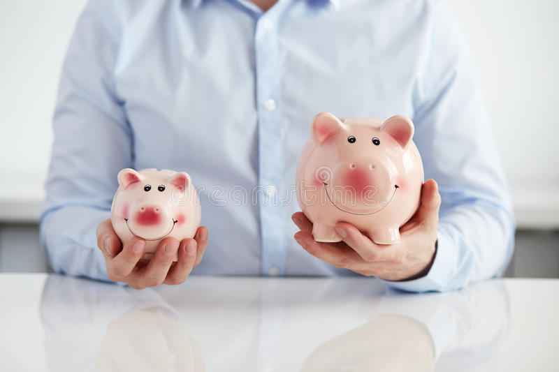 Man with two piggy banks stock images