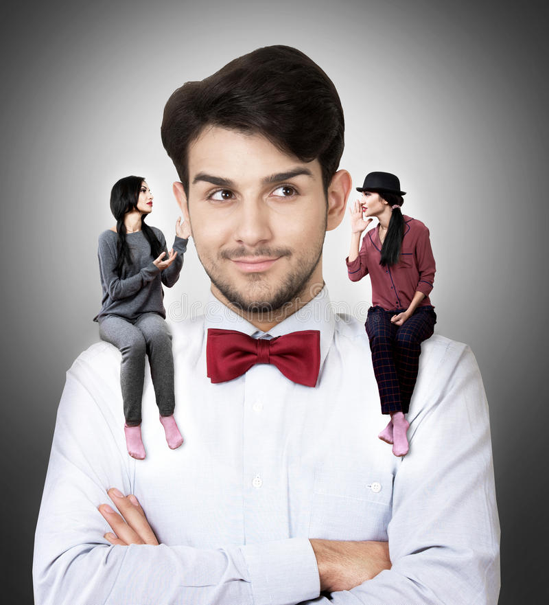 Man with two tiny girls on his shoulders. Young men in a bow tie with two talking women sitting on his shoulders royalty free stock image