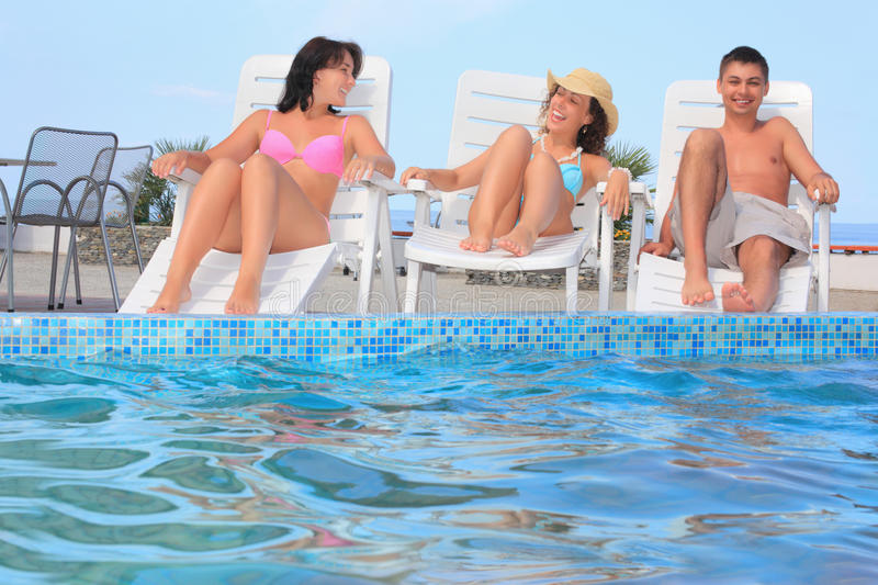 Download Man And Two Women Reclining On Chaise Lounges Stock Image - Image of horizontal, freedom: 13021569