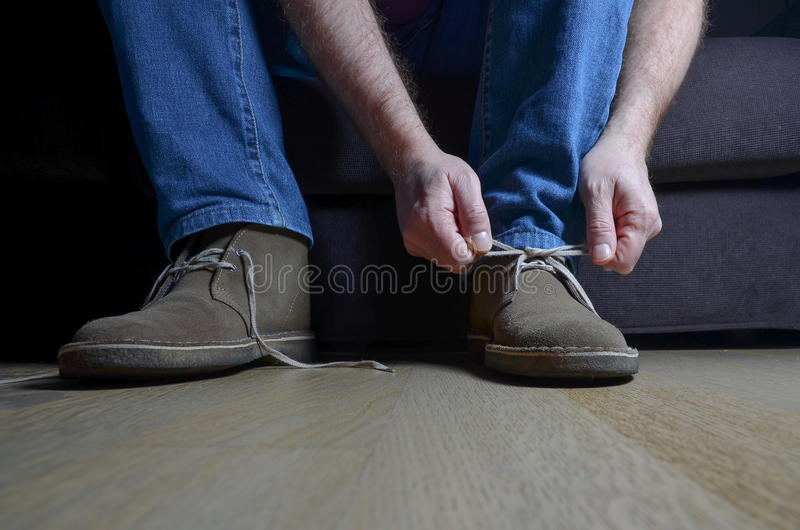 Man tying casual shoes stock images