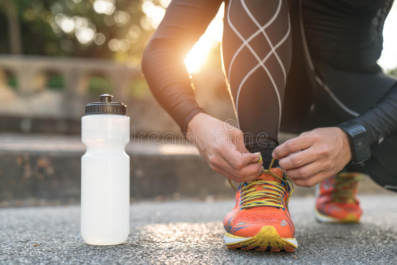 Man tying jogging shoes.A person running outdoors on a sunny day royalty free stock photography