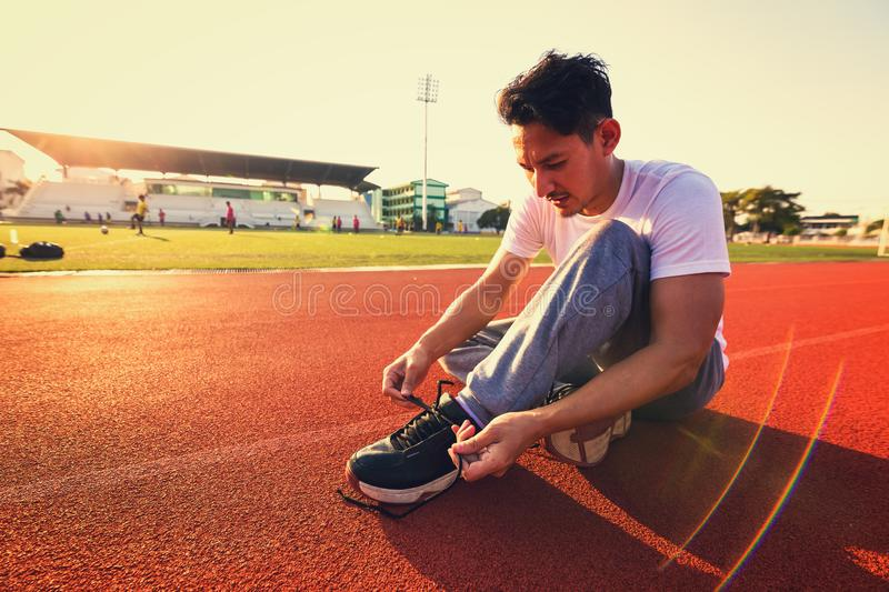 Man tying jogging shoes.A person sitting on racetrack and sun light. A Man tying jogging shoes.A person sitting on racetrack and sun light royalty free stock image