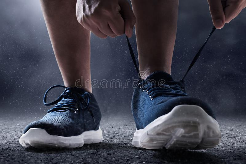 Man tying running shoes on asphalt background. S royalty free stock photos