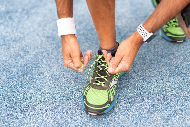 Man tying running shoes lace in the park outdoor stock images