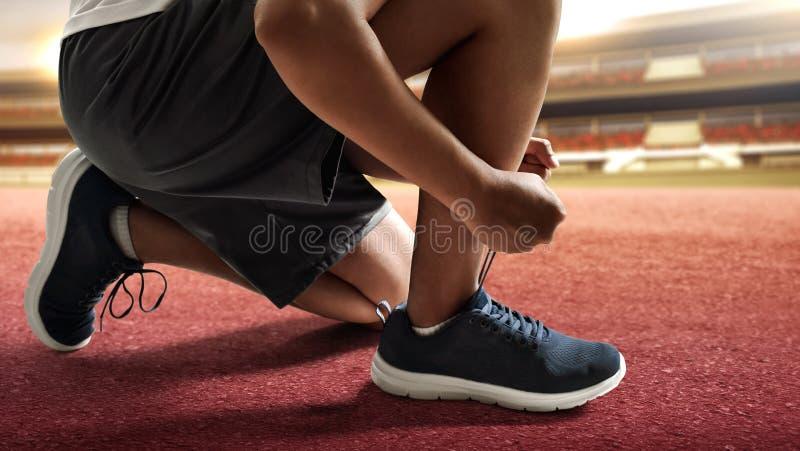 Man tying running shoes on racing track. Man tying running shoes on race track stock images