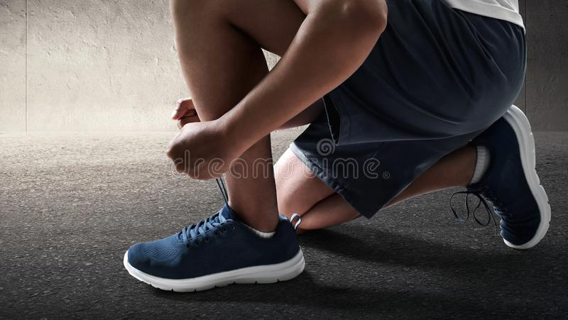 Man tying running shoes on road royalty free stock images