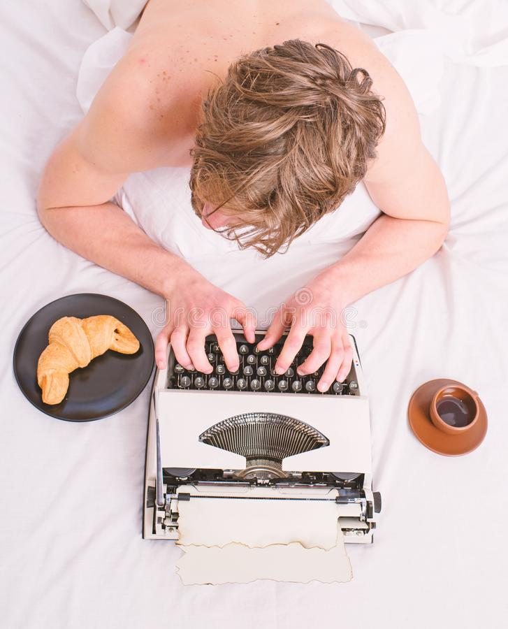 Man with typewriter and coffee lay bed. Author guy tousled hair busy write chapter deadline coming top view. Man. Inspired lay bedclothes work book. Writer royalty free stock image