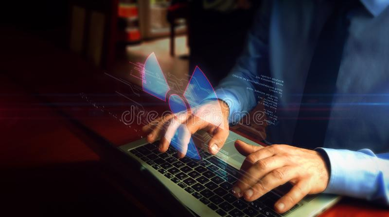 Man typing on keyboard with nuclear energy symbol hologram stock image