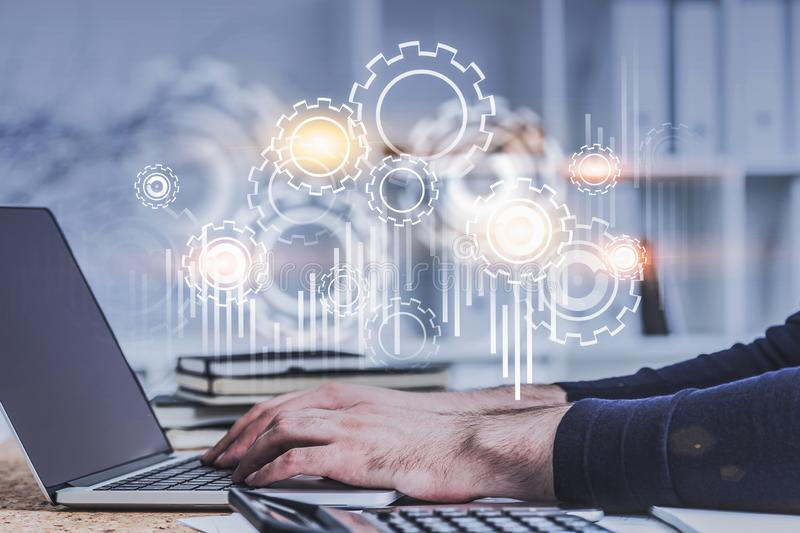 Man typing on laptop in office, gears. Hands of businessman typing on laptop in blurred office with double exposure of gears and graphs. Toned image stock photography