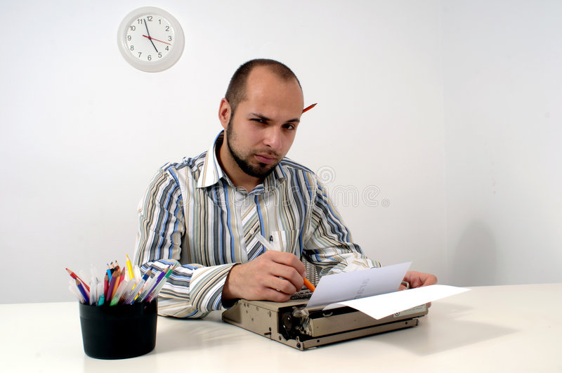 Man typing on Old Typewriter. Man typing a document on an antique typewriter in an office stock image