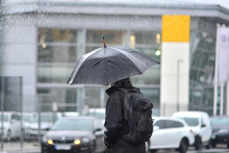 A man with an umbrella in the rain crossing the road. stock image