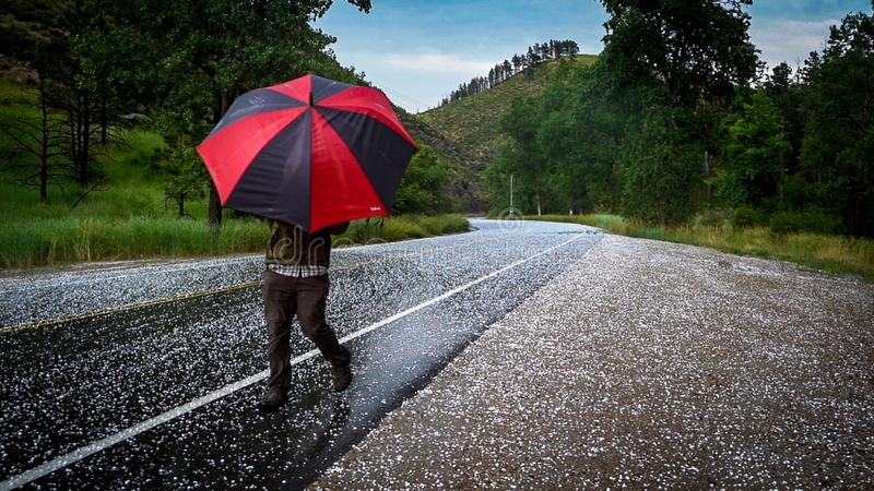 Man with umbrella on road with hail stock photos