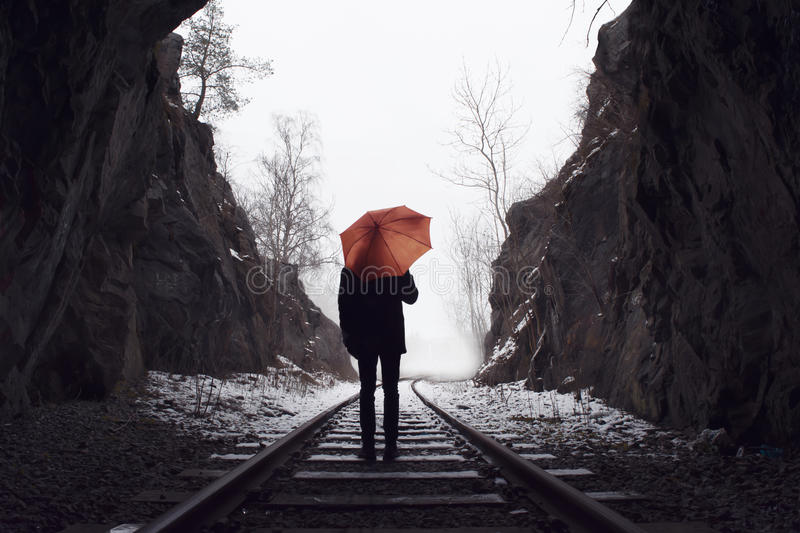 Man with umbrella standing on old railroad tracks vanishing. Man with bright colored umbrella standing on old, abandoned rails vanishing into the distance royalty free stock photos