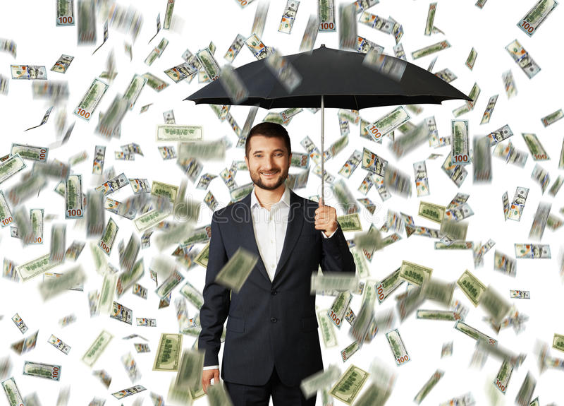 Man with umbrella standing under money rain. Successful smiley businessman with black umbrella standing under money rain stock image