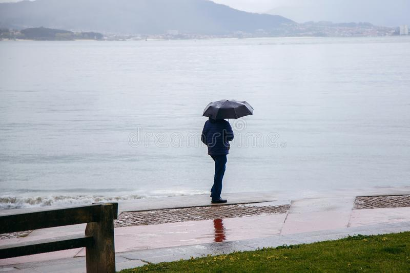 A man with an umbrella is walking along the embankment, it is raining, the Atlantic Ocean, bad weather stock photography