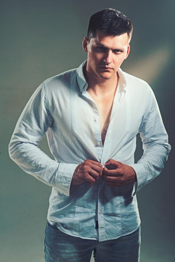 Man unbutton fashionable shirt. Young macho undress white shirt. Guy with serious face. Sexy model with elegant casual. Style. Fashion striptease and style stock photography
