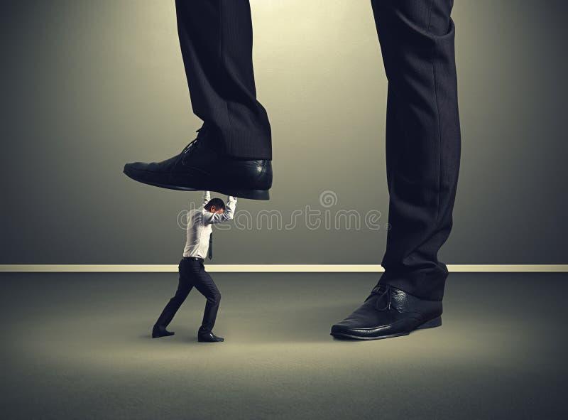 Man under big leg his boss stock photo