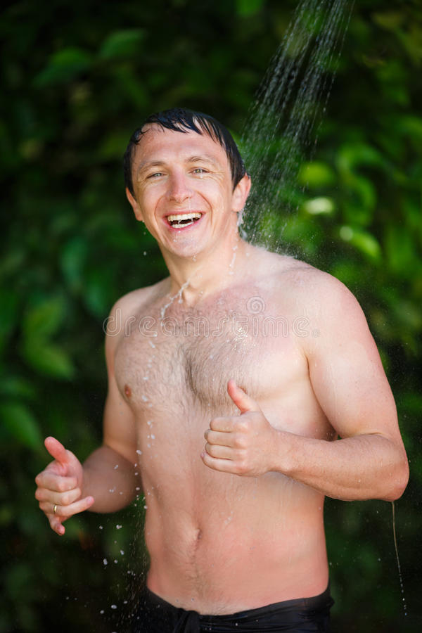 Man under a cold shower royalty free stock image
