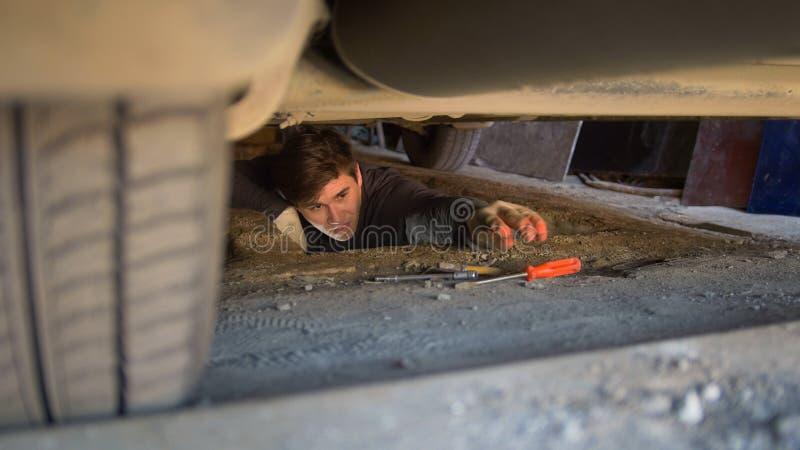 Man under en bil som når för en skruvmejsel för att reparera bilen arkivbild